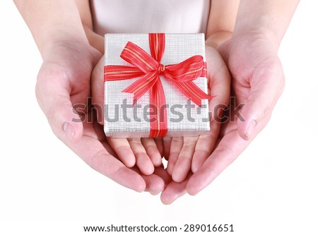 Hands holding beautiful gift box, adult and child giving gift, Christmas holidays and greeting season concept  - stock photo