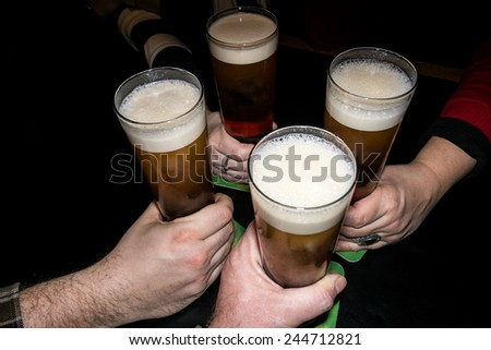Hands holding beer glasses drinking together in the pub - stock photo