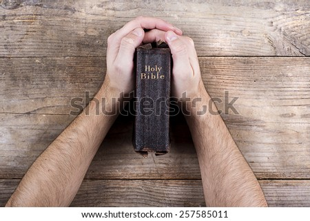 Hands holding Bible on a wooden desk background. - stock photo