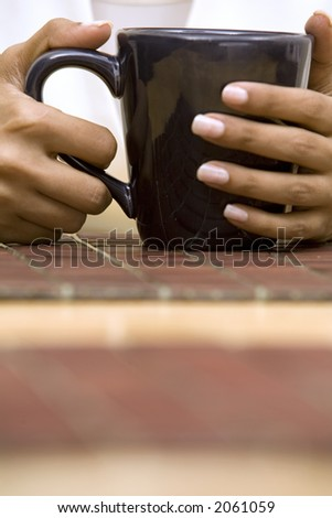hands holding black cup of coffee