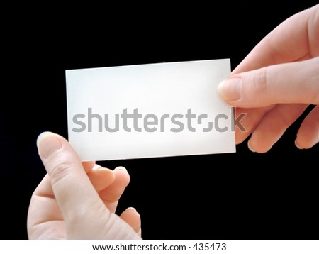 hands holding blank paper on black background