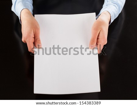 Hands holding blank sheet of paper, copy space - stock photo