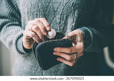 Hands holding british pound coin and small money pouch. Toned picture - stock photo