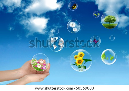 Hands holding bubbles against a blue sky - stock photo