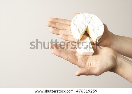 Hands holding camembert cheese - artistic light