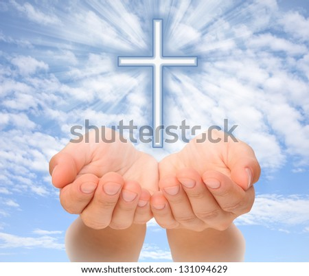 Hands holding Christian cross with light beams over sky - stock photo