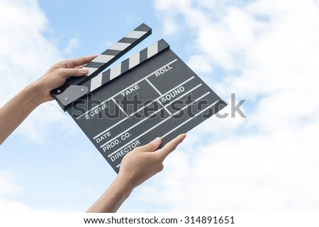 Hands holding clapper board on sky - stock photo