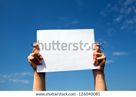 Hands holding clean white sheet paper over the sky. - stock photo