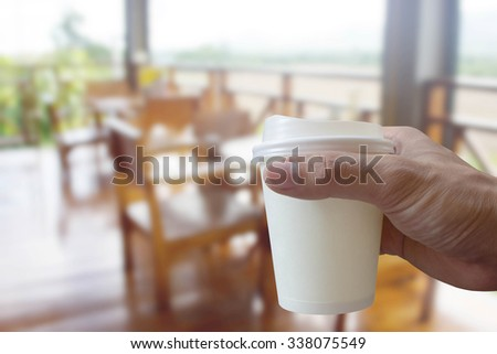 hands holding coffee cup with Coffee shop blur background
