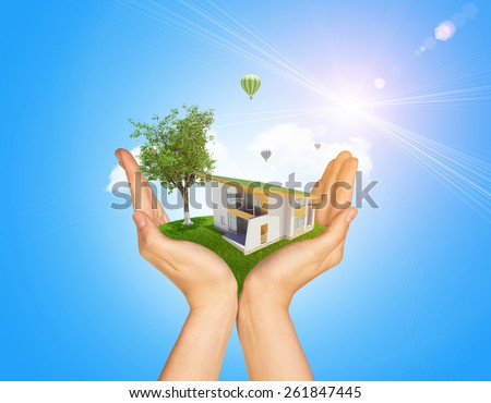 Hands holding cottage on green grass. Background of tree with leaves, hot air balloon and cloud. Blue sky - stock photo