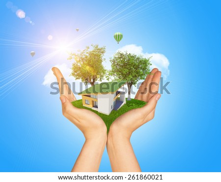 Hands holding cottage on green grass. Background of two tree with leaves, hot air balloon and cloud. Blue sky - stock photo
