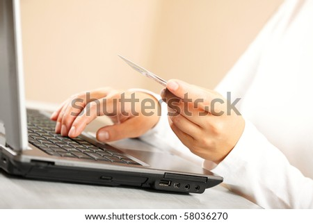 Hands holding credit card and laptop. Shallow DOF - stock photo