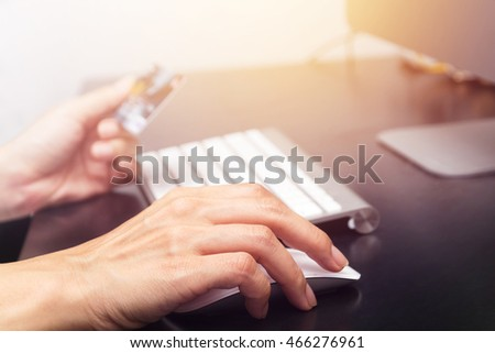 Hands holding credit card and using computer. On line shopping
