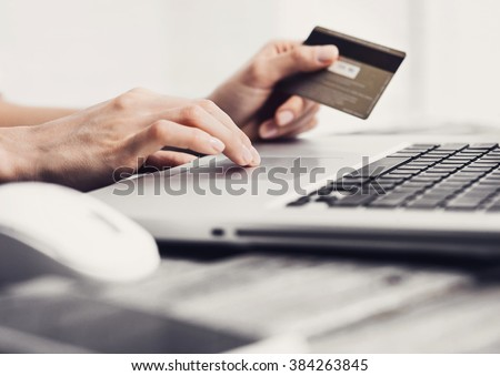 Hands holding credit card and using laptop. Online shopping concept - stock photo