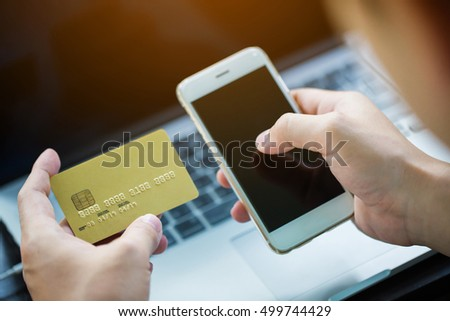 Hands holding credit card using on smart phone and laptop