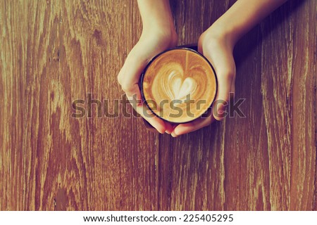 hands holding cup of coffee in coffee shop vintage color - stock photo