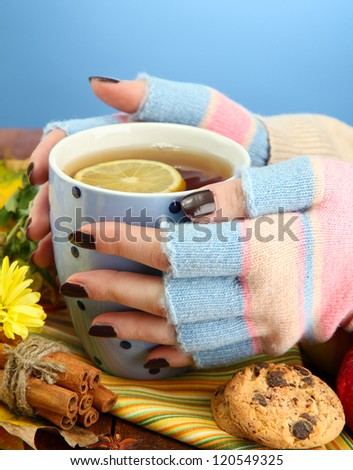 hands holding cup of hot drink and autumn leaves, on blue background - stock photo