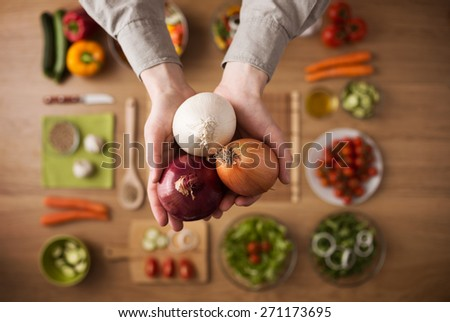 Hands holding different types of onions with fresh raw vegetables and salad bowls on background, top view - stock photo