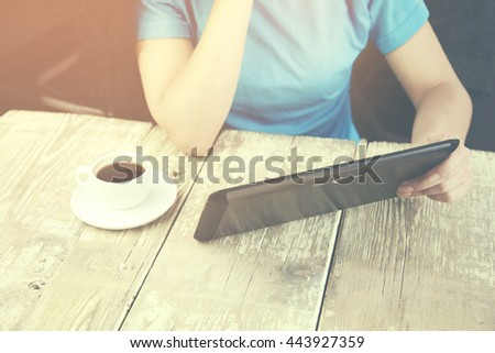 Hands holding digital tablet and coffee in office