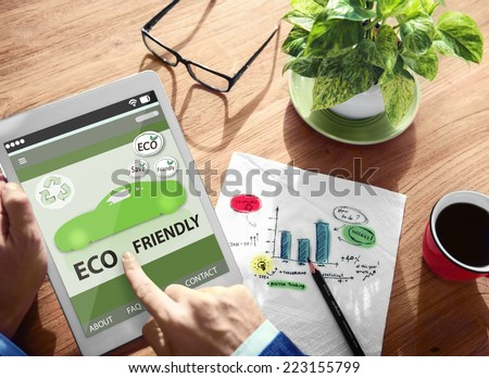 Hands Holding Digital Tablet Eco Friendly Car - stock photo