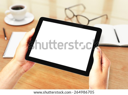 hands holding digital tablet in office, shallow depth of field - stock photo