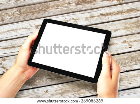 hands holding digital tablet on wooden table background - stock photo