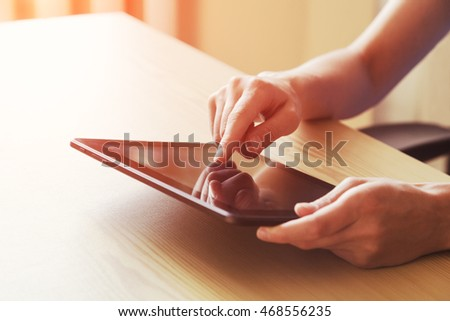 hands holding digital tablet touching with finger