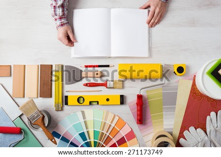 Hands holding DIY training open manual with work tools, color swatches and painting rollers at bottom, top view - stock photo