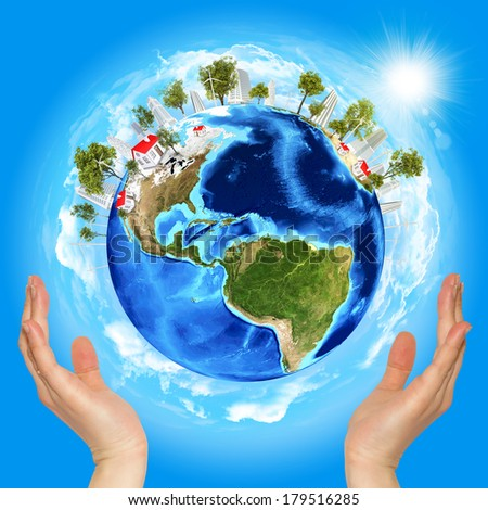 Hands holding earth. Blue sky on background - stock photo