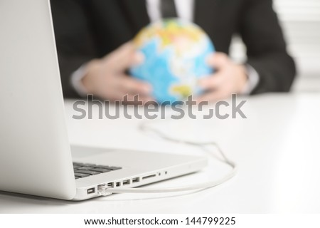 hands holding earth globe that connected to laptop computer