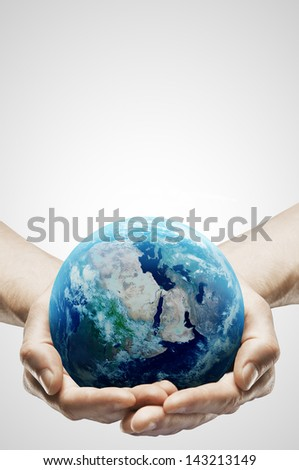 hands holding earth on gray background - stock photo
