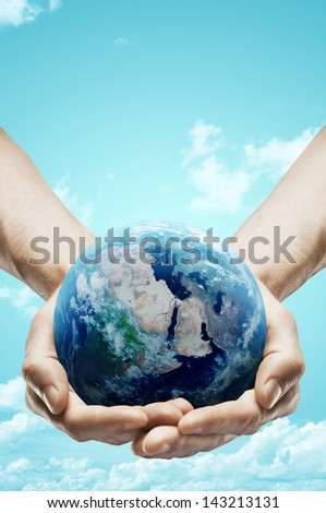hands holding earth on sky background