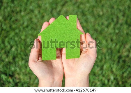 Hands holding eco house icon concept on the green grass background