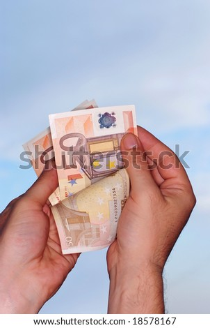 Hands holding euro against blue sky,clipping path included