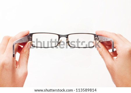 Hands holding eyeglasses on white background.