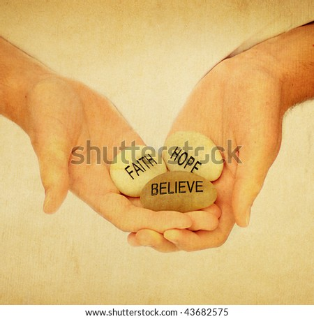 Hands holding faith hope and believe rocks - stock photo