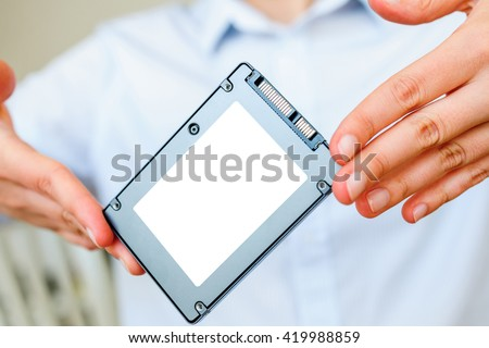 Hands holding fast flash SSD - solid state drive with sata 6 gb connection - blacnk place for diverse informateion and text to be inserted - stock photo