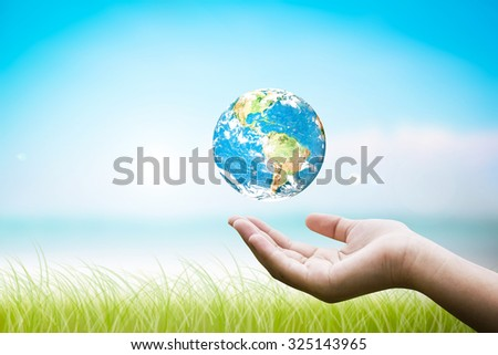 Hands holding floating earth. Abstract blurred background of ocean beach. World Conservation concept. beach with green grass. Designed to help the world reach:Elements of this image furnished by NASA - stock photo
