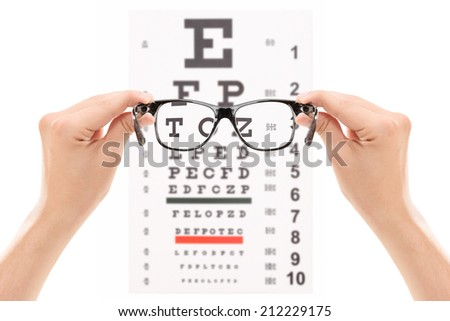 Hands holding glasses in front of an eye chart isolated on white background