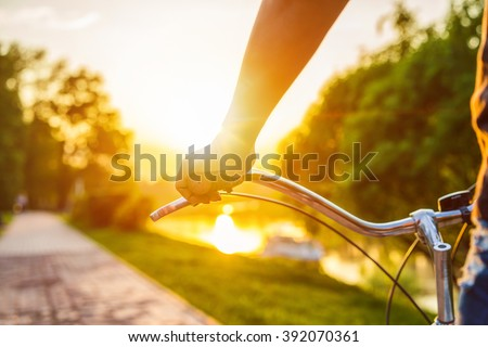 Hands holding handlebar of a bicycle at the summer sunset. - stock photo