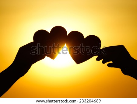 hands holding hearts silhouette - stock photo