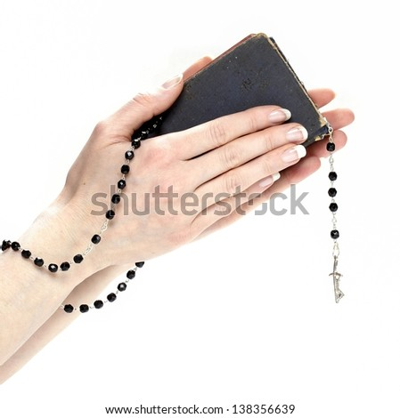 Hands holding Holy Bible and black rosary isolated on white background. - stock photo