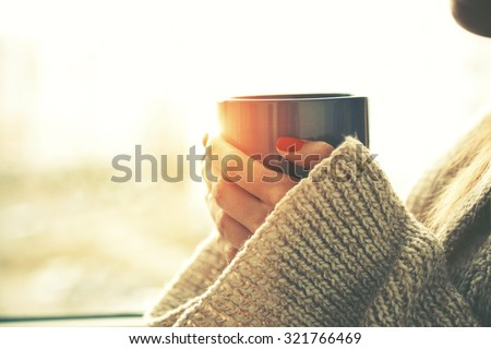 hands holding hot cup of coffee or tea in morning sunlight - stock photo