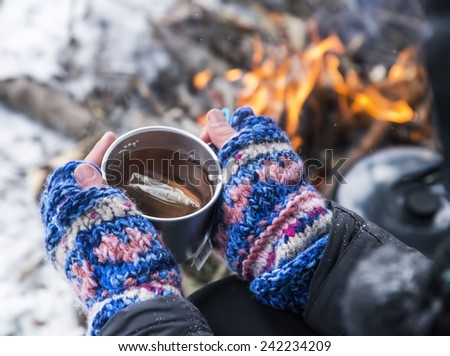 Hands Holding Hot Tea Cup Outdoor near Fire Place - stock photo