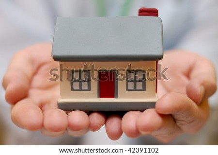 Hands holding house - stock photo