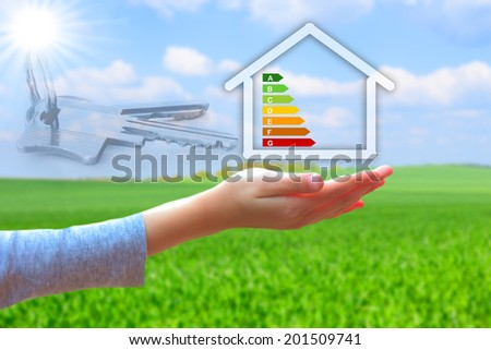 hands holding house with energy efficiency rating. - stock photo