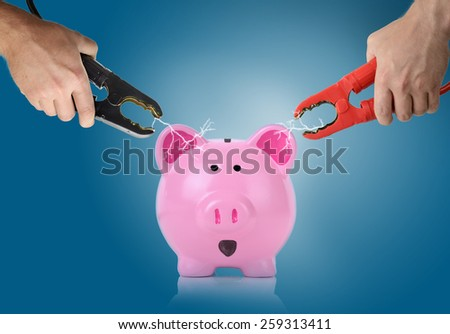 Hands holding jump start connectors with sparks between a piggy bank - stock photo