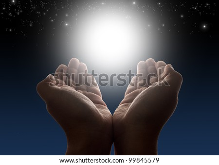 Hands holding light with night sky and stars in background - stock photo