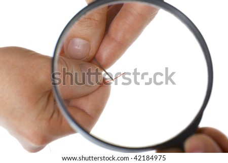 hands holding magnifying glass helping to put the thread through the needle isolated on white - stock photo