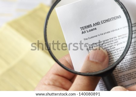 hands holding magnifying glass reading terms and conditions of loan agreement - stock photo